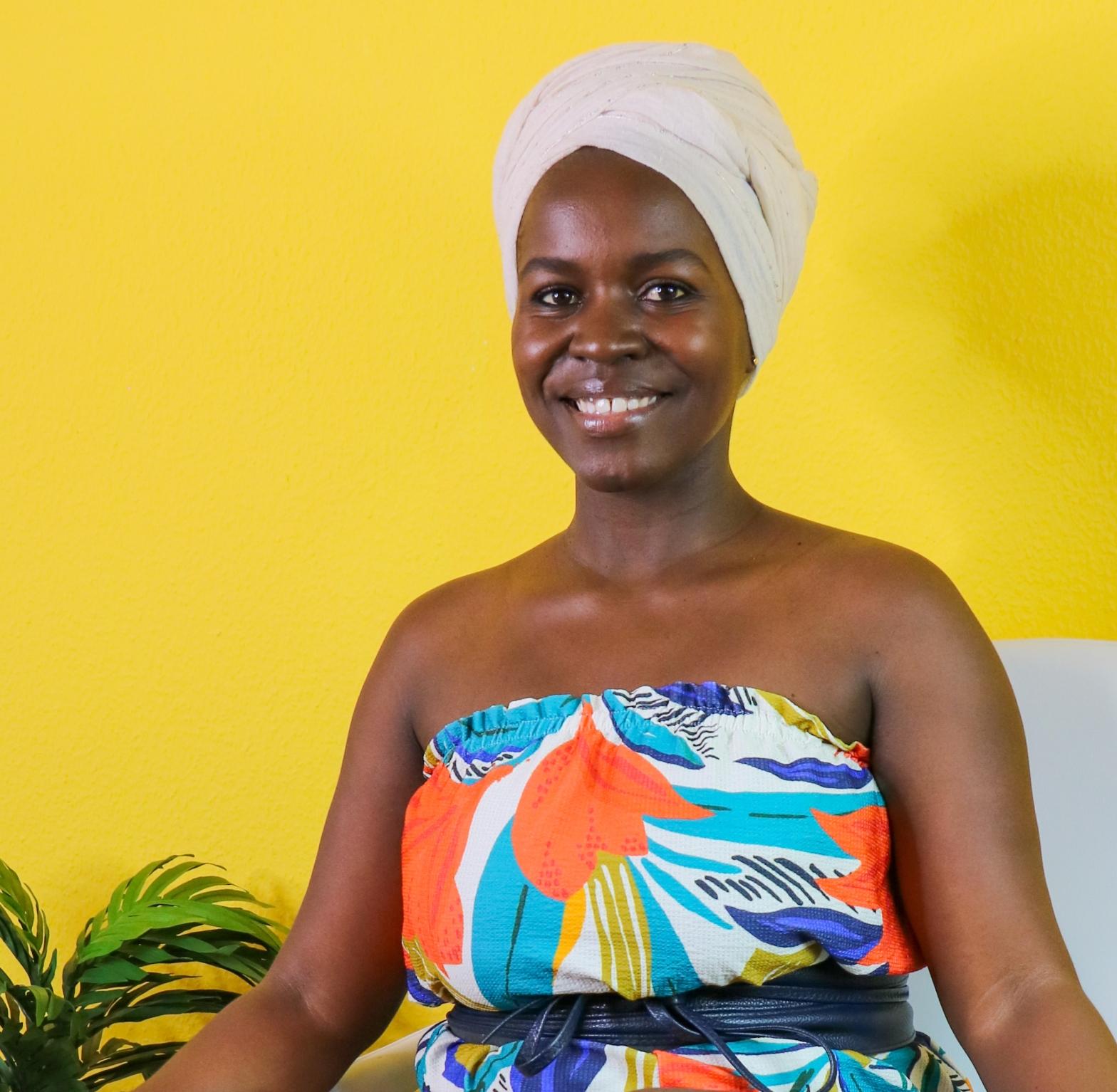 WanjikuMwaura sitted infront of a yellow background